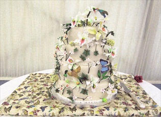 Wedding cake with hand-sculpted icing flowers, orchids and humming birds